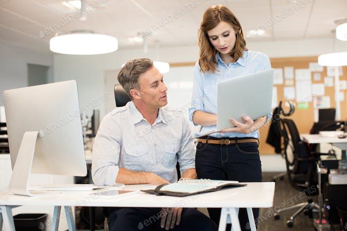 Geschäftsfrau diskutiert mit männlichen Kollegen während der Arbeit im Büro