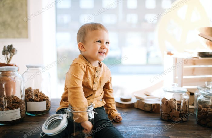 A small toddler boy sitting on a table in zero waste shop.