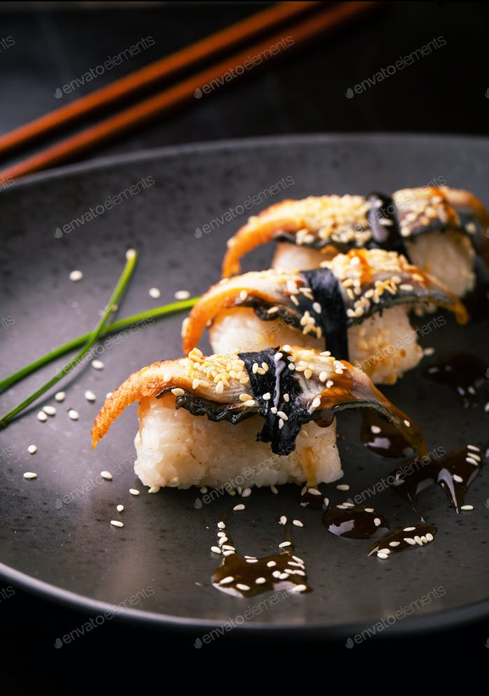 Sushi with smoked eel. Unagi nigiri with sauce
