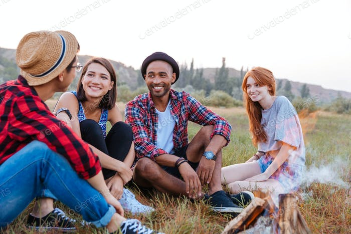 Happy young people sitting near campfire together
