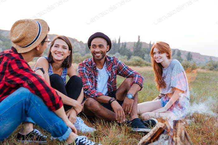 Glückliche junge Leute sitzen in der Nähe des Lagerfeuers zusammen
