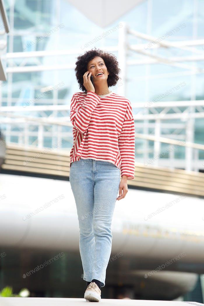 Ganzkörper-Afro-amerikanische Frau zu Fuß in der Stadt mit Handy
