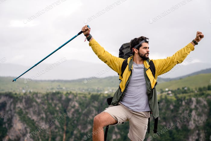 Sports, success and achievement concept. Young hiker, happy with that he successfully achieved top