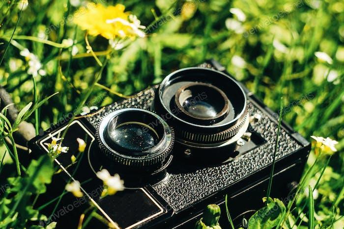 Mittelformat Film Fotokamera auf grünem Gras mit Blumen