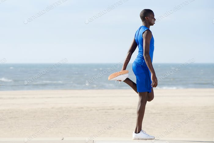 Healthy young man exercising on the beach