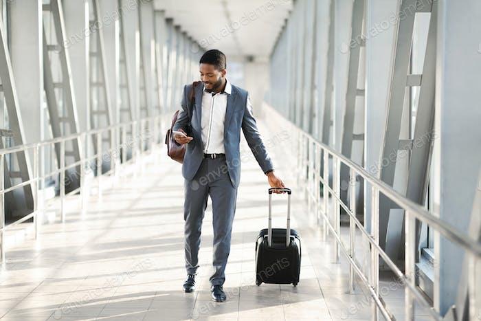 Unternehmer mit Smartphone Walking In Flughafen Mit Koffer Indoor