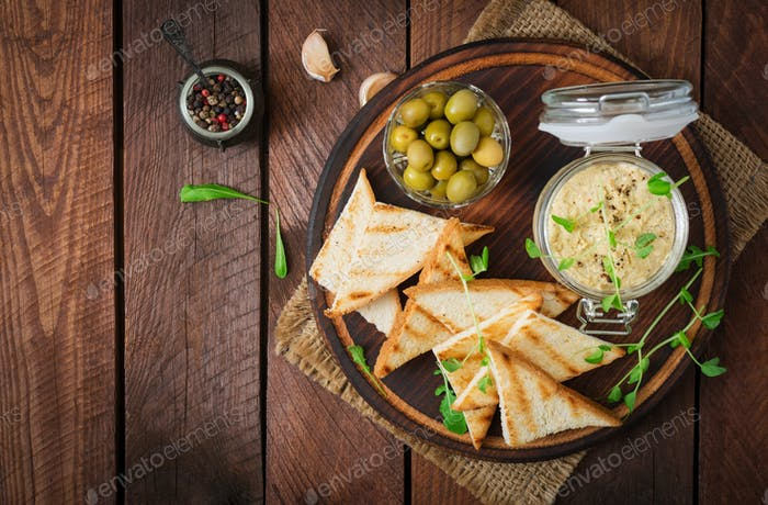 Pate Chicken - rillette, toast, olives and herbs on a wooden board. Flat lay. Top view