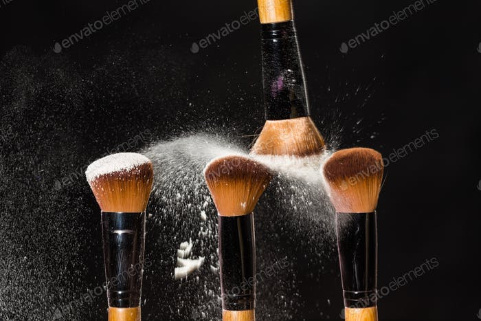 Mineral cosmetics concept - Make-up brush with powder explosion on black background