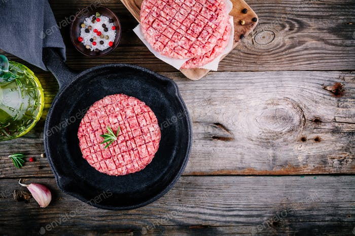 Raw ground beef meat burger steak cutlets In a cast-iron frying pan