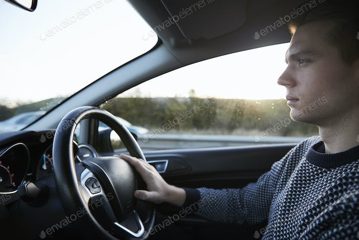 Interior View Of Young Man Driving Car On Motorway
