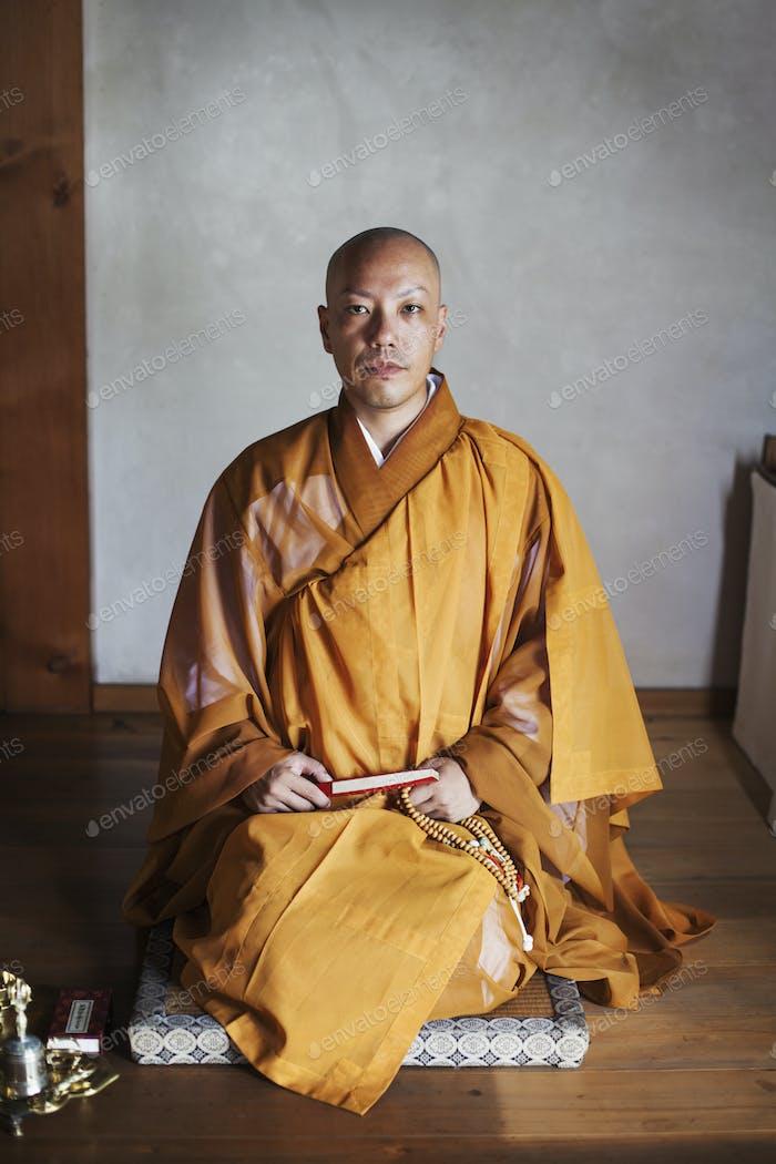 Buddhistischer Mönch in einem goldenen Gewand Anbetung