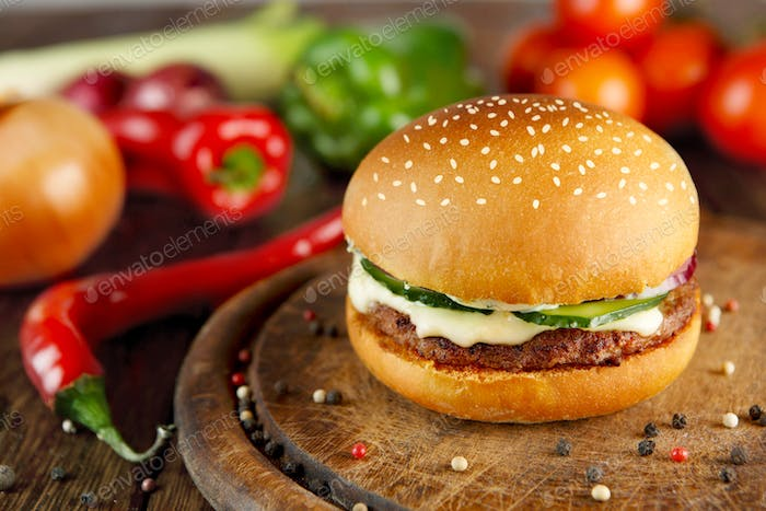 Meet and cheese burger at wooden desk