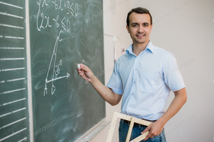 Young teacher or student holding triangle pointing at chalkboard with formula, looking to camera and
