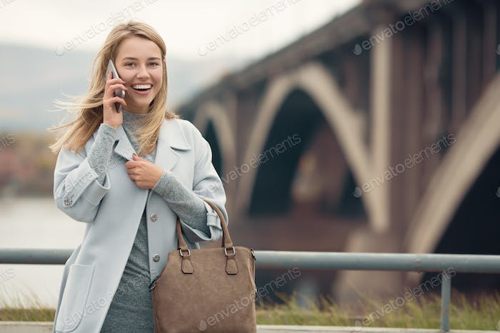 Young Woman In Blue Coat Talking Phone. Autumn City Background.