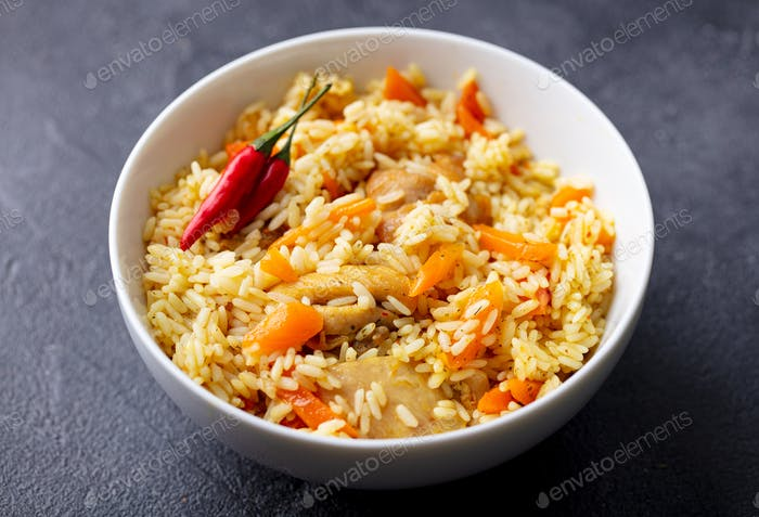 Chicken and Rice Pilaf, Plov on white bowl. Grey background. Close up.