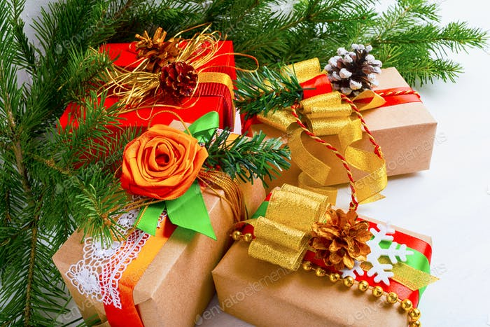 Christmas gift boxes with golden ribbon, white snowflake and fir