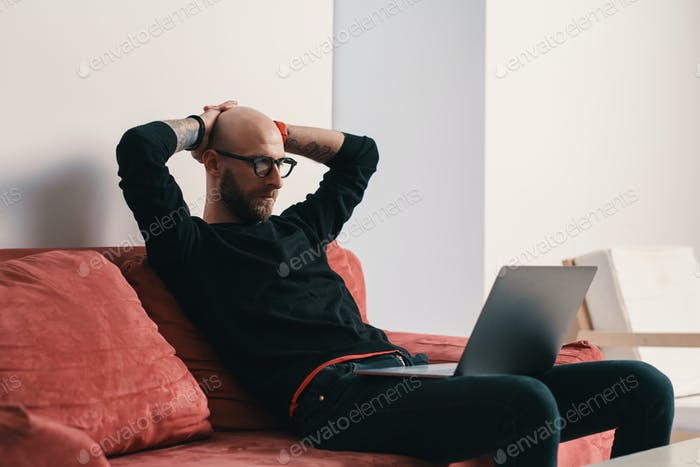 Modern man sitting on couch with laptop relaxing with hands behind head