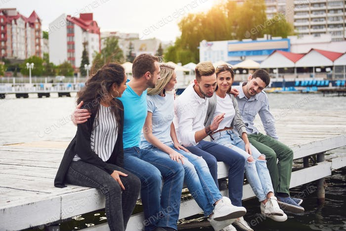 Group of happy young friends on the pier, pleasure in playing creates emotional life