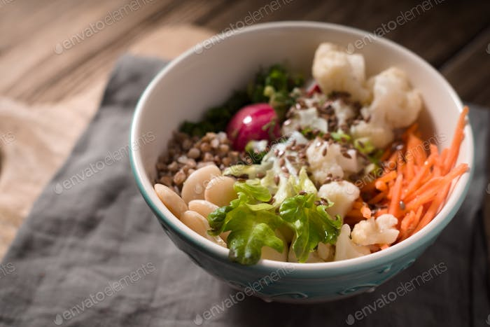 Healthy salad with buckwheat and vegetables on the blurred background