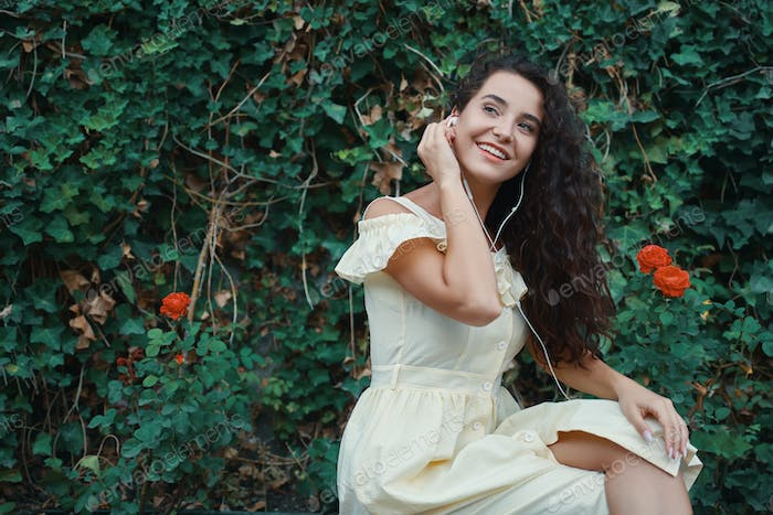 Romantic young woman with an adorable smile and gorgeous long curly hair