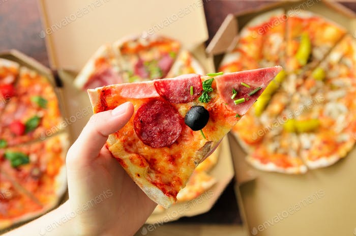 Female hand taking slice of fresh pizza from delivery box. Top view, dark background. Junk food