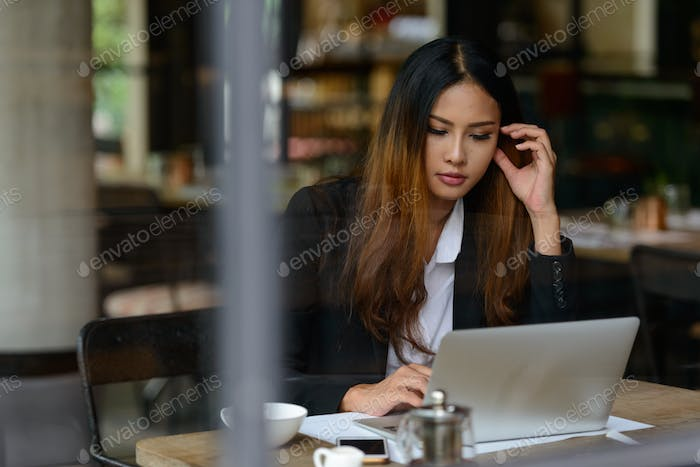 Young beautiful Asian businesswoman using laptop at the coffee shop