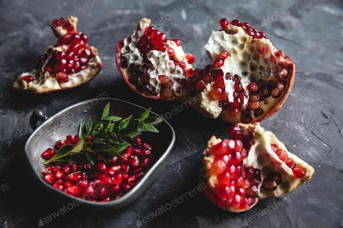 Food photo of red ripe pomegranate pieces in bowl on the gray table with copy space. Healthy food