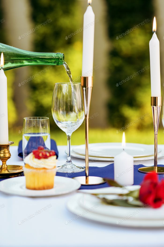 Table setting, wine is poured into a wineglass