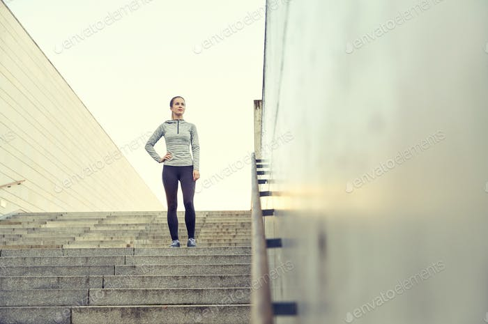 sporty woman standing on in city stairs