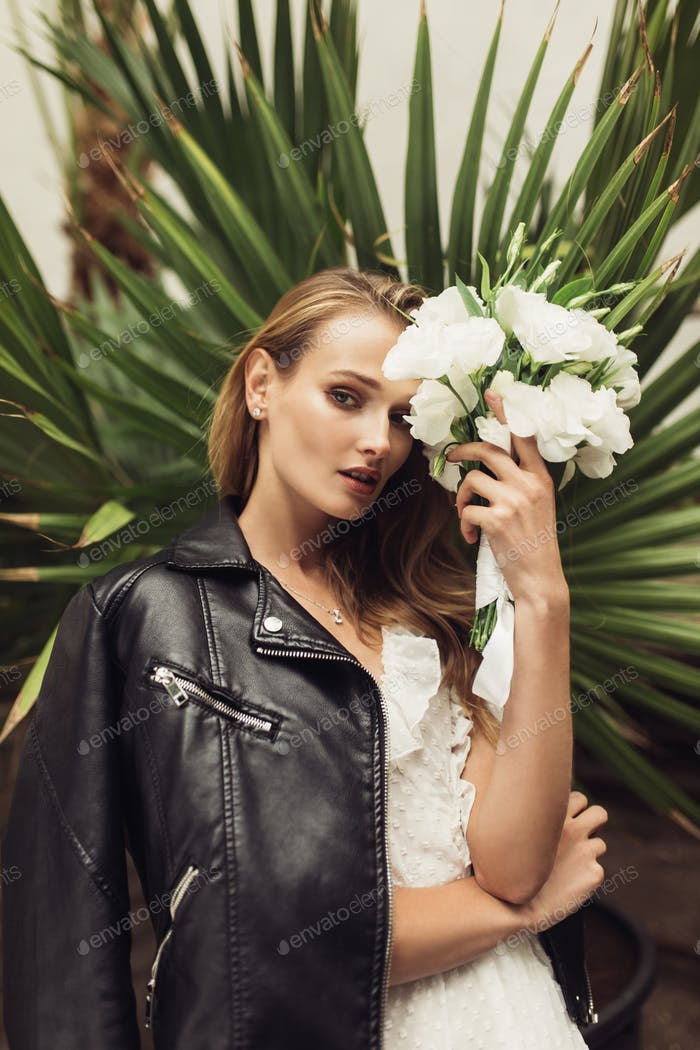 Young beautiful woman in white dress with black leather jacket o