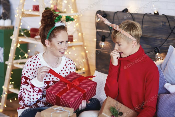 Two excited girls opening christmas present