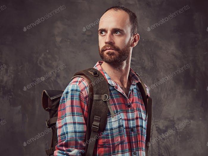 Retrato de un apuesto viajero tatuado en una camisa de franela con una mochila, de pie en un estudio.