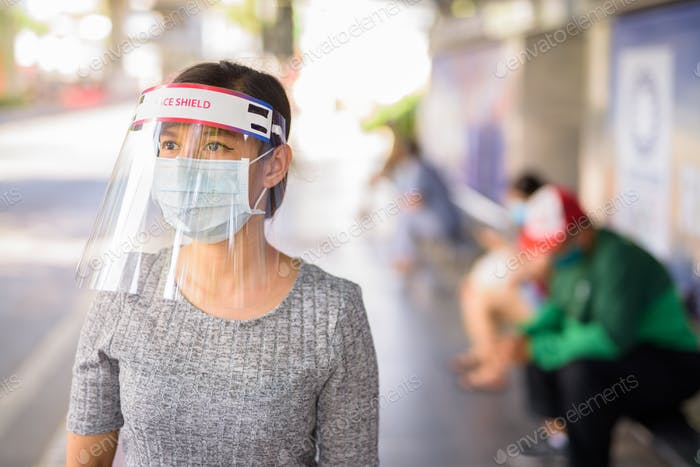 Young Asian woman with mask and face shield waiting at the bus stop