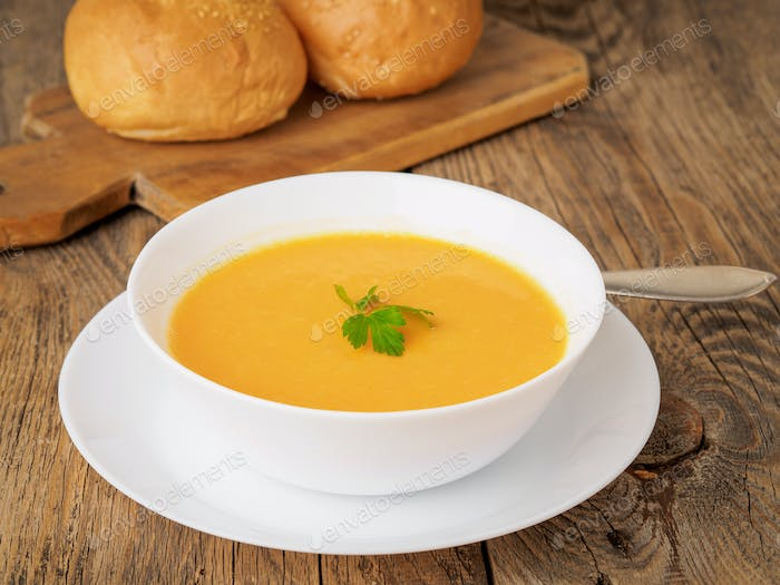 white bowl of pumpkin soup, garnished with parsley on wooden background, side view.