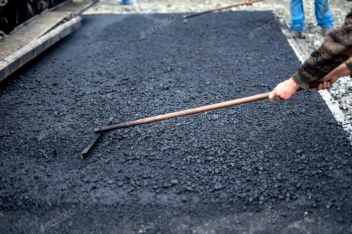 Arbeiter Nivellierung frischen Asphalt auf einer Straßenbaustelle, Industriegebäude