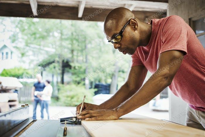Man wearing glasses working in a lumber yard.