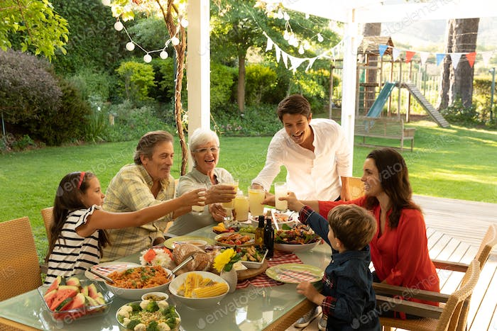 Family eating outside together in summer