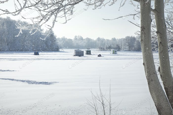 Ice fishing houses at a Minnesota lake on a bright winter morning