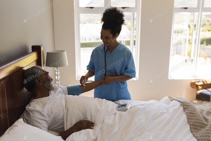 Female doctor measuring blood pressure of senior man in bedroom at home