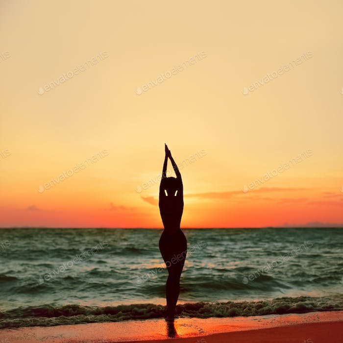Beautiful slim girl at sunset on the beach