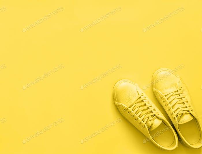yellow sneakers on yellow background, copy space
