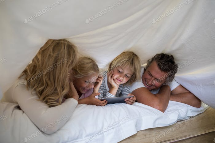 Happy family using digital tablet under blanket in bedroom