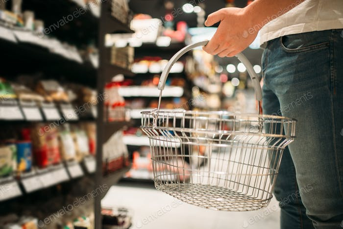 Male customer with empty basket in supermarket