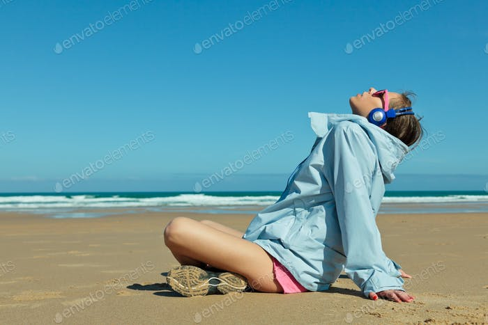 Fitness girl with headphones on the beach