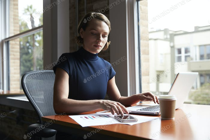 Businesswoman Working On Laptop And Checking Mobile Phone