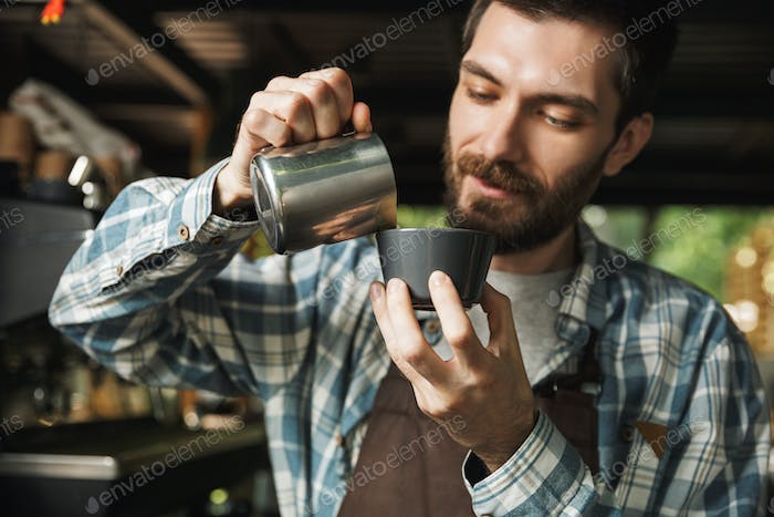 Image of brunette barista man making coffee while working in caf