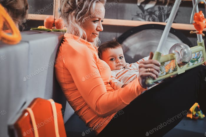Cheerful mom is playing with her baby while waiting for a doctor