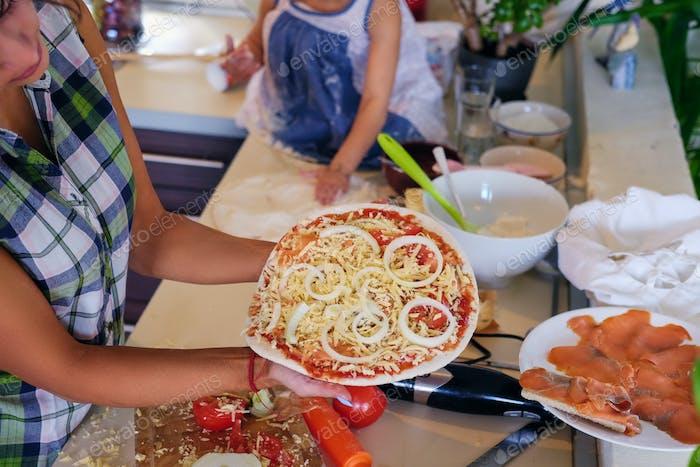 Familia feliz cocinando comida en una cocina casera.
