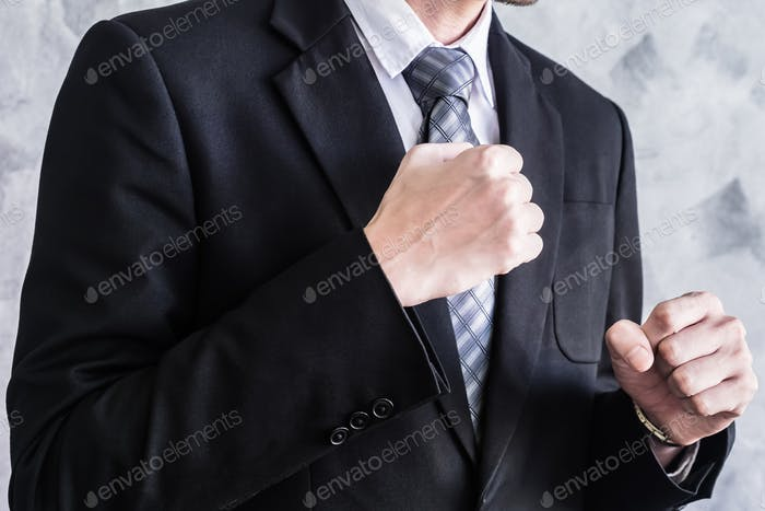 Close up of businessman in black suit Fighting on grunge background.