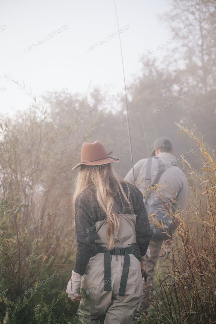 A couple, a man and woman walking along a riverbank with fishing gear.